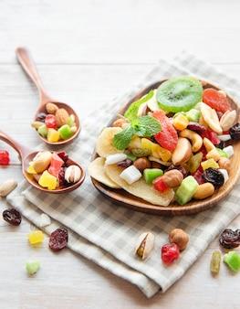 Ciotola con vari tipi di frutta secca e noci su una superficie di legno