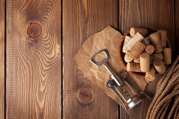 Ciotola con tappi per vino e cavatappi. vista dall'alto su sfondo tavolo in legno rustico con spazio copia