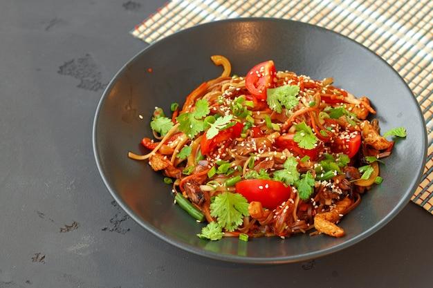 Ciotola di tagliatelle wok con verdure su sfondo nero da vicino