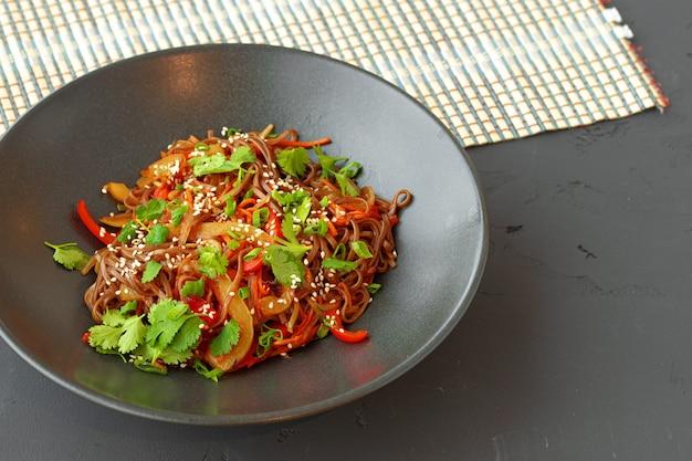 Ciotola di tagliatelle wok con verdure sulla superficie nera