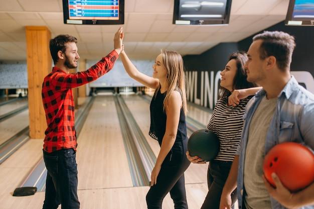 Il giocatore di bocce lancia la palla in corsia e fa strike. la squadra di bowling si congratula a vicenda, lancio di successo. uomini e donne che giocano nel club, tempo libero attivo
