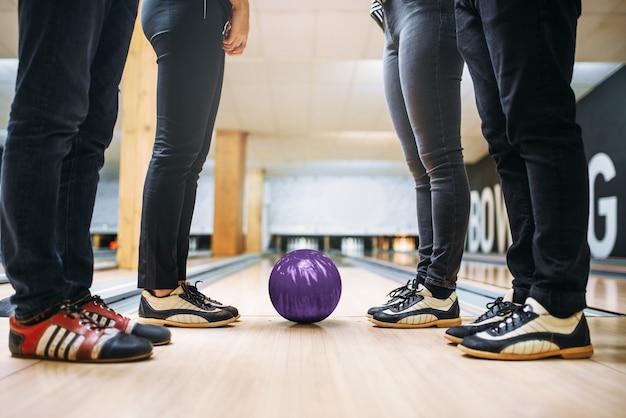 Squadra di bowling, piedi dei giocatori in scarpe da casa e palla in corsia. amici che giocano nel club, tempo libero attivo