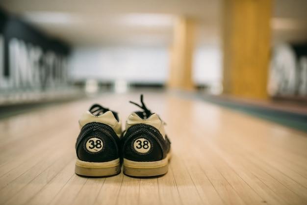Palla da bowling e scarpe da casa sulla corsia vista del primo piano
