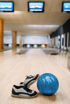 Palla da bowling e scarpe da casa sul pavimento di legno