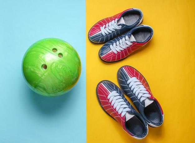 Scarpe da bowling e palla da bowling su giallo blu. sport per famiglie al coperto.