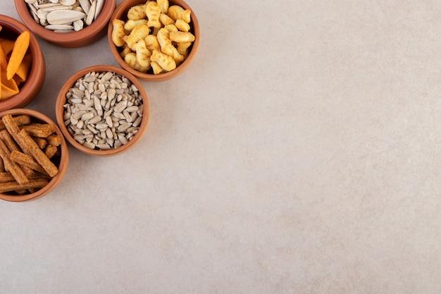 Ciotole di patatine, cracker e semi di girasole sulla superficie della pietra.