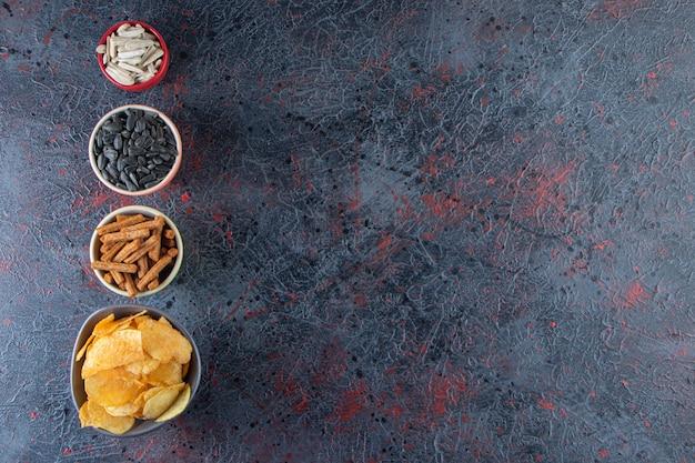 Ciotole di patatine, cracker e semi di girasole sulla superficie scura.