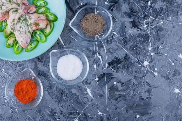 Ciotole piene di spezie diverse accanto al piatto con ali e peperoni su sfondo blu.