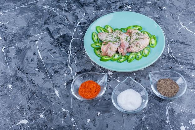 Ciotole piene di spezie diverse accanto al piatto con ali e peperoni sul blu.