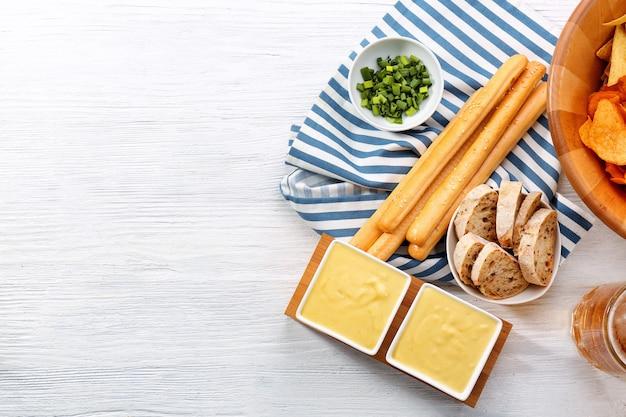 Ciotole con salsa di formaggio alla birra e snack sul tavolo di legno