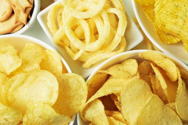 Ciotole con diversi snack sulla superficie bianca, da vicino