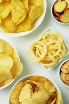 Ciotole con diversi snack sulla superficie bianca