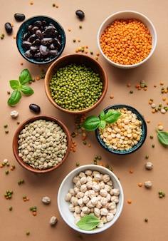 Ciotole con diversi tipi di legumi su una superficie marrone