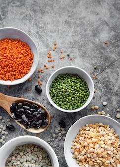 Ciotole con diversi tipi di legumi su una superficie di cemento grigio