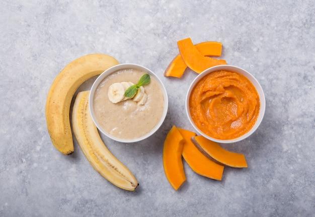 Ciotole con alimenti per bambini sani sulla tavola di colore. le puree, fatte di frutta e verdura biologica fresca, scuoiano laici, vista dall'alto, concetto. pasto per bambini