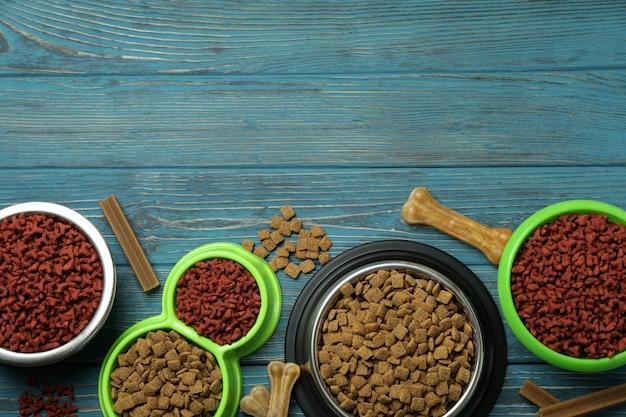 Ciotole con mangimi per animali su fondo in legno