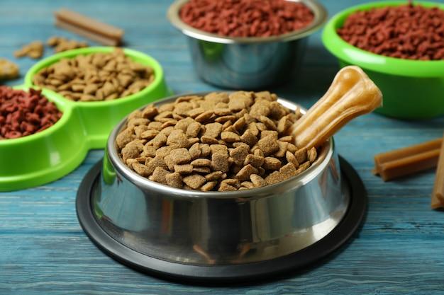 Ciotole con mangimi per animali su legno