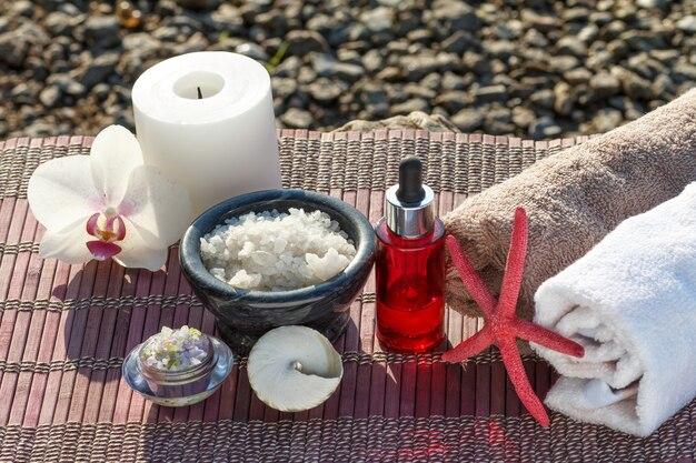 Ciotole con sale marino, bottiglie con olio aromatico, candela, fiore di orchidea, conchiglia, stella marina e asciugamani con panno di bambù su pietre. prodotti spa su sfondo naturale
