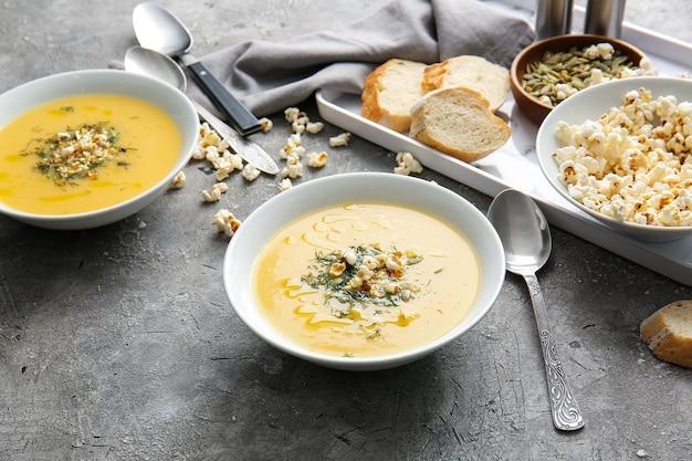 Ciotole con gustosa zuppa di popcorn su sfondo grigio