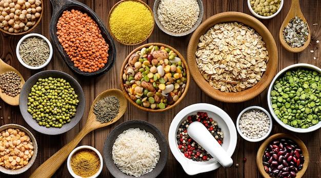 Ciotole con vari legumi e cereali colorati sulla tavola di legno. vista dall'alto. lay piatto