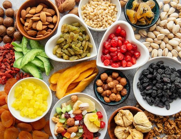 Ciotole con vari tipi di frutta secca e noci su una scrivania di cemento grigio
