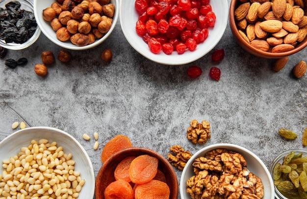 Ciotole con vari tipi di frutta secca e noci su una superficie di cemento grigio