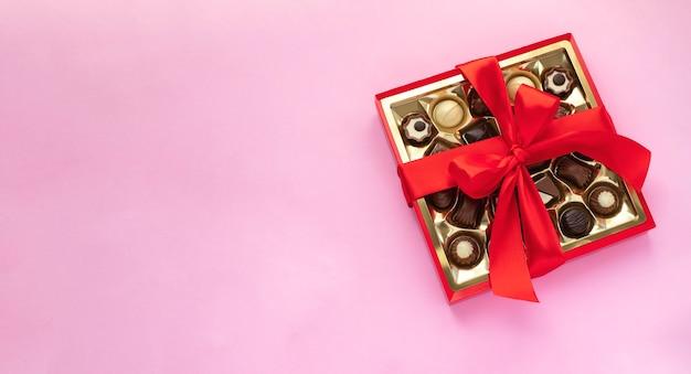 Scatola di praline di cioccolato con fiocco rosso sul rosa