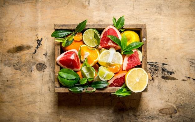 Una scatola di agrumi - pompelmo, arancia, mandarino, limone, lime e foglie