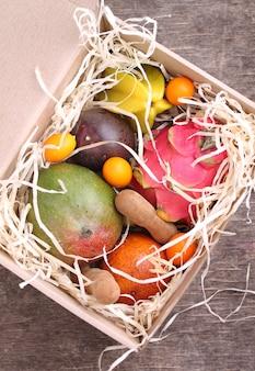 Scatola di frutta esotica (mango, frutto della passione, carambola, arancia, kumquat, frutto del drago)