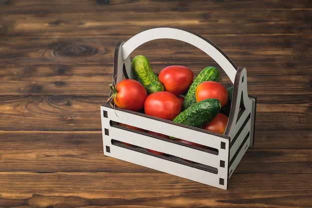 Una scatola piena di cetrioli e pomodori su un tavolo di legno.