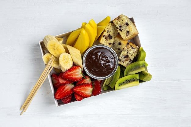 Scatola di frutta con cioccolato pronto da mangiare, da asporto. fragole; mango; banana; kiwi; biscotto. concetto di consegna. cibo salutare