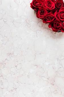 Scatola di rose rosse su sfondo rosa