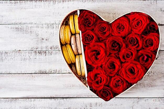 Scatola a forma di cuore con rose rosse e maccheroni. regalo di san valentino. vista dall'alto