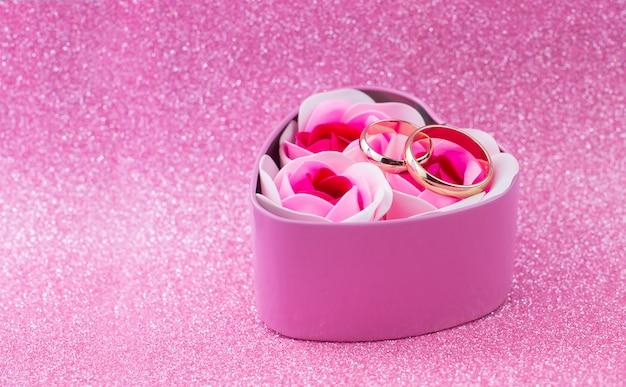 Scatola regalo a sorpresa cuore rosa con fedi nuziali in oro con rose su uno sfondo lucido con bokeh per san valentino