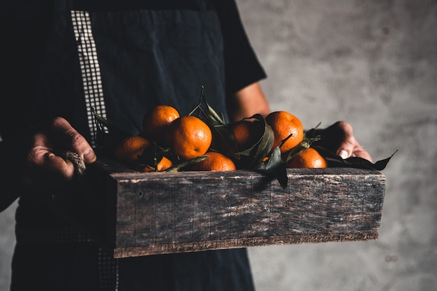 Una scatola di mandarino in mani maschili su uno sfondo grigio. agricoltore, frutta ecologica, cibo. pnov2019