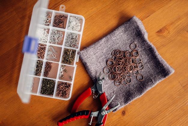Scatola con accessori per cucito e pinze sul tavolo di legno, vista dall'alto. gioielli fatti a mano. artigianato, bigiotteria