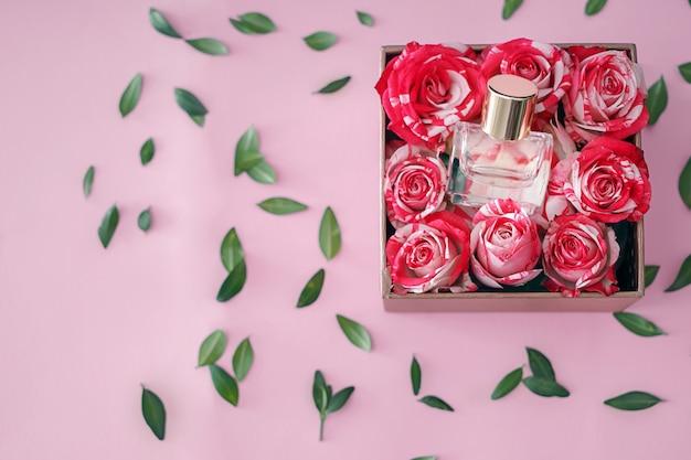 Scatola con bottiglia di profumo e rose su rosa