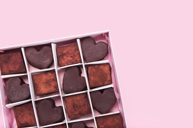 Scatola con dolci al cioccolato a forma di cuore su sfondo rosa. concetto di san valentino. copia spazio.