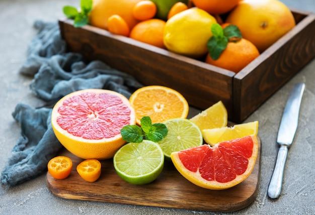 Scatola con frutta fresca di agrumi su uno sfondo concreto