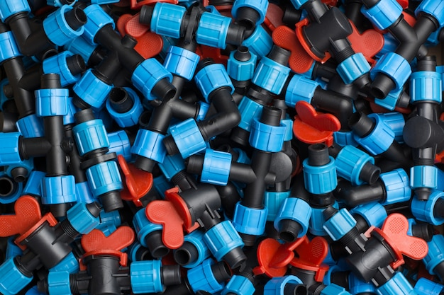 Scatola con diverse attrezzature per l'irrigazione a goccia di costruzione. rubinetti dell'acqua, tee, interruttori e altre attrezzature in plastica. vista dall'alto
