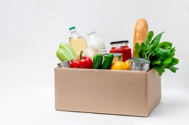 Scatola con forniture alimentari. prodotti essenziali: olio, conserve, cereali, latte, verdure, frutta