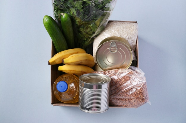 Scatola con scorte alimentari. riso, grano saraceno, pasta, cibo in scatola, banana, cetrioli, uova, olio vegetale.