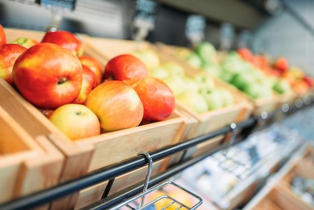 Scatola con mele rosse fresche in stand nel negozio di alimentari, nessuno. assortimento di frutta nel mercato