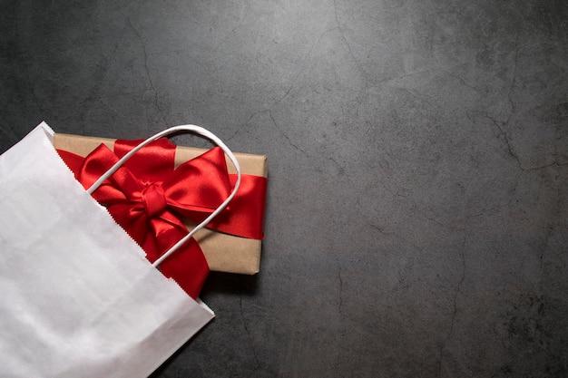 Scatola con un regalo con un nastro rosso in un negozio, una vista dall'alto su uno sfondo scuro