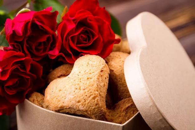 Scatola con biscotti a forma di cuore. dessert vicino alle rose. crea la tua ricetta delle feste. grande dolce sorpresa.