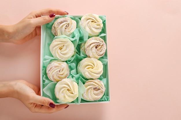Scatola con marshmallow fatti in casa in mani femminili su uno sfondo pastello, orientamento orizzontale, vista dall'alto, copia dello spazio