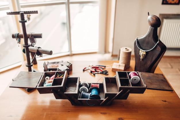 Scatola con strumenti di ricamo, attrezzature artigianali e accessori sulla tavola di legno, nessuno. gioielli di eleganza fatti a mano