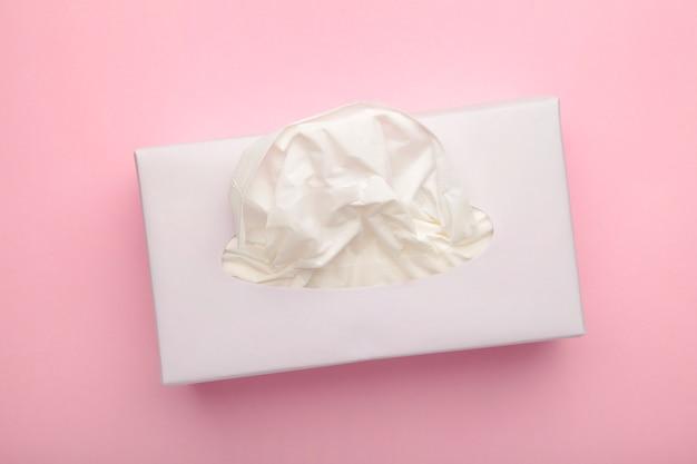Scatola con fazzoletti di carta su sfondo rosa pastello.