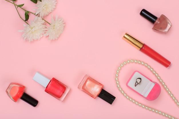 Scatola con anello, perline, bottiglie con smalto, rossetto e fiori su sfondo rosa. cosmetici e accessori donna. vista dall'alto.