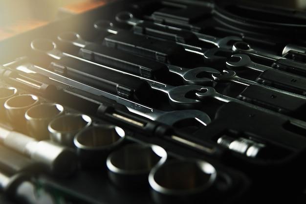 Scatola con set di strumenti per la riparazione dell'auto, primo piano, chiave bassa con abbagliamento della lente.